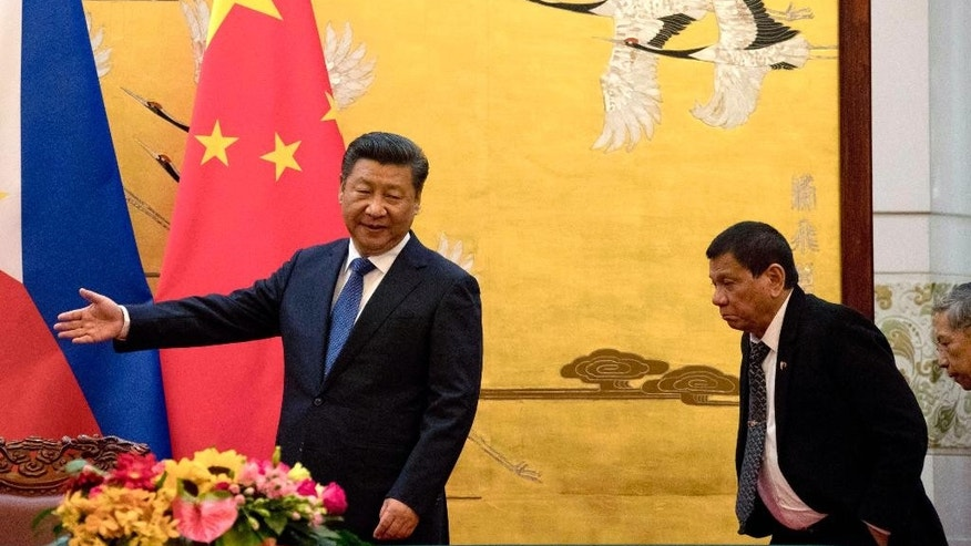 FILE - In this Thursday, Oct. 20, 2016 file photo, Philippine President Rodrigo Duterte, right, is shown the way by Chinese President Xi Jinping before a signing ceremony in Beijing, China.  Japanese officials are wary ahead of the arrival of outspoken Duterte. Their concern is not only about his foreign policy toward the U.S., but also about his informal style. They are paranoid about him chewing gum in front of the Emperor. Duterte arrives in Tokyo later Tuesday for a three-day visit, his first as Philippine leader. (AP Photo/Ng Han Guan, Pool, File)