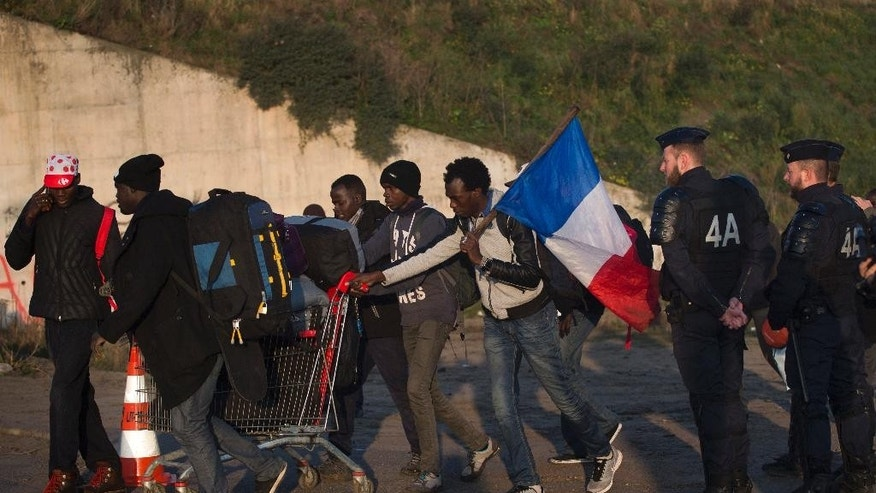 """Migrants, one of them carrying a French flag, walk past French police as they leave a makeshift camp known as """"the jungle"""" to register at a processing center, near Calais, northern France, Tuesday, Oct. 25, 2016. France began the mass evacuation Monday of the makeshift migrant camp, a mammoth project to erase the humanitarian blight on its northern border, where thousands fleeing war or poverty have lived in squalor, most hoping to sneak into Britain. (AP Photo/Emilio Morenatti)"""