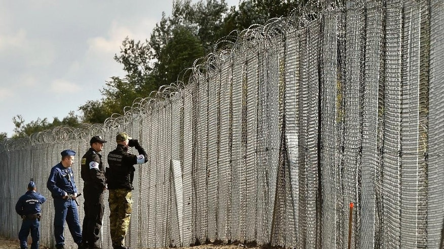 FILE - In this Oct. 13, 2016 file picture a police officer, second right, and border guard, right, of Poland patrol with Hungarian policemen along the temporary border fence on the Hungarian-Serbian border near Roszke, 180 kms southeast of Budapest, Hungary. Hungary has started building a new fence on its southern border with Serbia, part of its  efforts to keep migrants and refugees from freely entering the country. Hungarian state television said Tuesday Oct. 25, 2016   two kinds of barriers were being tested along a  short stretch of the border before construction begins in earnest. Prime  Minister Viktor Orban said in August that the new fence was needed in case of a  new surge of people moving toward Western Europe.  (Zoltan Mathe/MTI via AP,file)