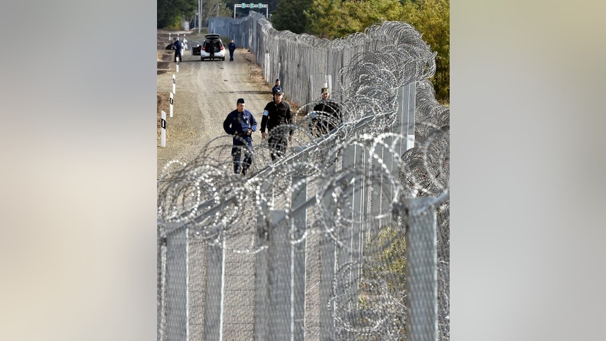 FILE - In this Oct. 13, 2016 file picture a police officer, left  and border guard, right, of Poland patrol  along the temporary border fence on the Hungarian-Serbian border near Roszke, 180 kms southeast of Budapest, Hungary. Hungary has started building a new fence on its southern border with Serbia, part of its  efforts to keep migrants and refugees from freely entering the country. Hungarian state television said Tuesday Oct. 25, 2016   two kinds of barriers were being tested along a  short stretch of the border before construction begins in earnest. Prime  Minister Viktor Orban said in August that the new fence was needed in case of a  new surge of people moving toward Western Europe.  (Zoltan Mathe/MTI via AP,file)