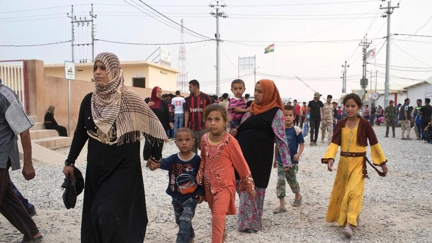 People arrive at a camp for displaced families in Dibaga, near Mosul, Iraq, Monday, Oct. 24, 2016. The campaign to retake Mosul comes after months of planning and involves more than 25,000 Iraqi troops, Kurdish forces, Sunni tribal fighters and state-sanctioned Shiite militias. It is expected to take weeks, if not months, to drive Islamic State militants out of Iraq's second largest city, which is still home to more than a million people.(AP Photo/Marko Drobnjakovic)