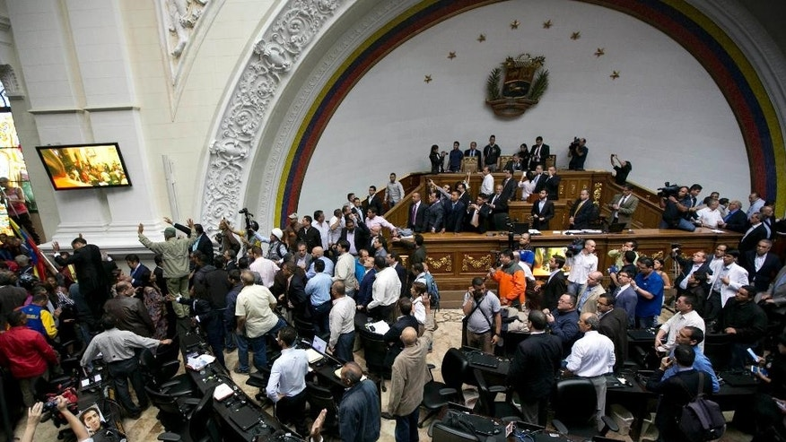 Lawmakers stand as a group of government supporters force their way into the National Assembly in Caracas, Venezuela, Sunday, Oct. 23, 2016. Government supporters interrupted a special congressional session where lawmakers were discussing bringing legal charges against President Nicolas Maduro. (AP Photo/Ariana Cubillos)