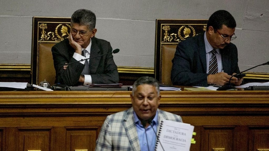 "Ruling party lawmaker Pedro Carreño speaks during a special session of Congress as Henry Ramos Allup, president of Congress, top left, looks on in Caracas, Venezuela, Tuesday, Oct. 25, 2016. After the government suspended a recall referendum seeking the president's removal last week, the opposition-controlled congress began debating Venezuelan President Nicolas Maduro's ""constitutional situation."" Lawmakers vow to present evidence that he's a dual Colombian citizen and therefore constitutionally ineligible to hold Venezuela's highest office.  (AP Photo/Alejandro Cegarra)"
