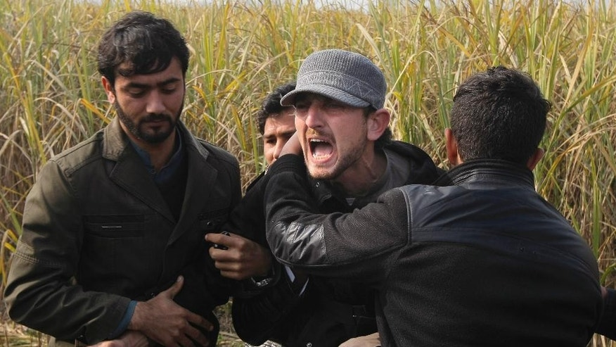 FILE -- In this Jan. 21, 2016 file photo, people comfort a man mourning the death of his family member who was killed in an attack on Bacha Khan University, during a funeral in Charsadda, Pakistan. On Tuesday, Oct. 25, 2016, militants wearing suicide vests and firing automatic rifles storm a Pakistani police academy in the southwestern city of Quetta overnight killed at least 59 people and wounded over 100 more, mostly police cadets and recruits. There were conflicting claims of responsibility on Tuesday for the attack. Militant attacks have in the past 3 years claimed the lives of hundreds of people, including many schoolchildren. (AP Photo/Mohammad Sajjad, File)
