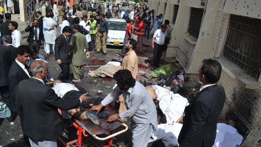 FILE -- In this Aug. 8, 2016 file photo, people help victims of a bomb blast at a government-run hospital that killed dozens of people, in Quetta, Pakistan. On Tuesday, Oct. 25, 2016, militants wearing suicide vests and firing automatic rifles storm a Pakistani police academy in the southwestern city of Quetta overnight killed at least 59 people and wounded over 100 more, mostly police cadets and recruits. There were conflicting claims of responsibility on Tuesday for the attack. Militant attacks have in the past 3 years claimed the lives of hundreds of people, including many schoolchildren. (AP Photo/Arshad Butt, File)