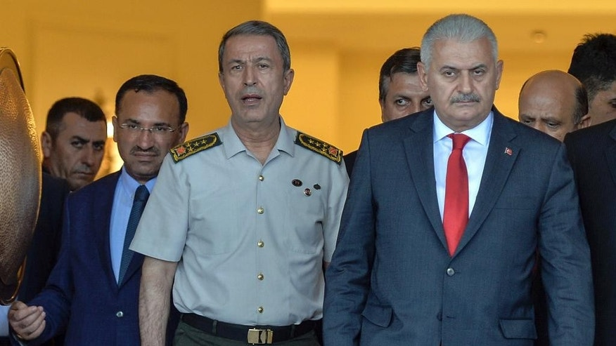 "FILE - In this July 16, 2016 file photo, Turkey's Prime Minister Binali Yildirim, right, Chief of Staff Gen. Hulusi Akar, center, and Justice Minister Bekir Bozdag arrive for a press conference hours after a failed coup attempt in Ankara, Turkey. Bozdag says Tuesday, Oct. 25, 2016 the country has provided ""more than sufficient"" evidence to the United States for the extradition of a U.S.-based Muslim cleric accused by Turkey of orchestrating the July 15 failed coup attempt. Bozdag was speaking to reporters Tuesday before departing to the U.S. for talks with U.S. Attorney General Loretta Lynch over Turkish requests for Fethullah Gulen's arrest and eventual extradition. (AP Photo/File)"
