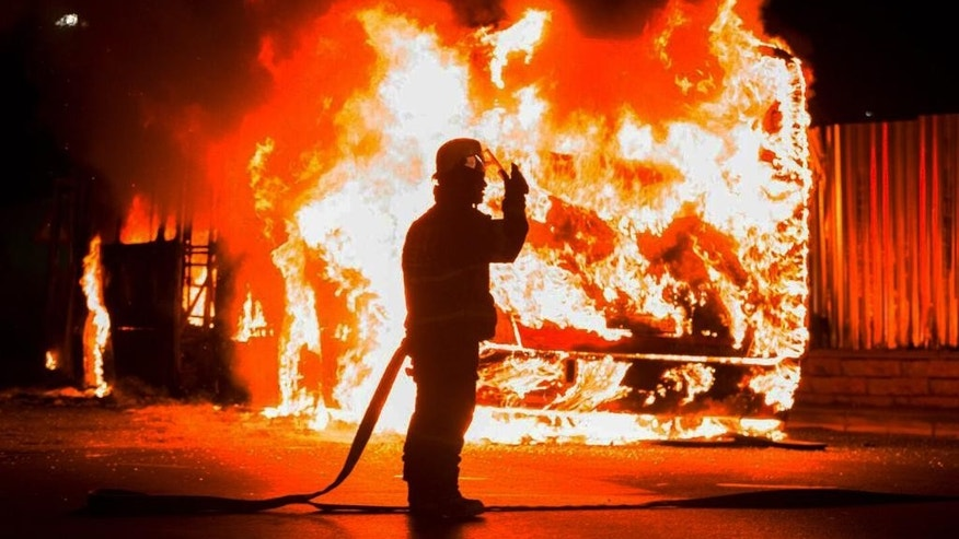 A fireman stands at a burning bus in Braamfontein, Johannesburg, South Africa, Tuesday, Oct. 25, 2016. Rioters in South Africa set a police vehicle on fire Tuesday and stoned vehicles near a Johannesburg university that has been the scene of sometimes violent protests by students demanding free education. The violence broke out in streets near the University of the Witwatersrand at around the same time that student protesters met and marched off the campus, South African media reported. (AP Photo/Yeshiel Panchia)