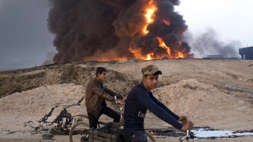 FILE - In this Sunday, Oct. 23, 2016 file photo, youths ride bicycles next to a burning oil well in Qayara, about 31 miles (50 km) south of Mosul, Iraq. The Islamic State group has pioneered brutally innovative tactics and launched diversionary attacks that have shocked its opponents, and now many fear it has more surprises in store as Iraqi forces close in on Mosul. Last week's assault on the northern city of Kirkuk offers a glimpse at the kind of asymmetrical response it might mount as Iraqi forces close in on Mosul, its last major urban bastion in the country. (AP Photo/Marko Drobnjakovic, File)