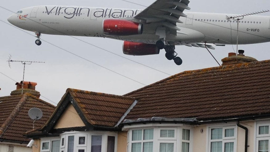 An Airbus A330-300 of Virgin Atlantic on final approach to landing skims over the rooftops of nearby houses at Heathrow Airport in London, Tuesday, Oct. 25, 2016. Britain's government will reveal how it plans to expand London's airport capacity Tuesday, more than a year after a special commission recommended a third runway at Heathrow. (AP Photo/Frank Augstein)