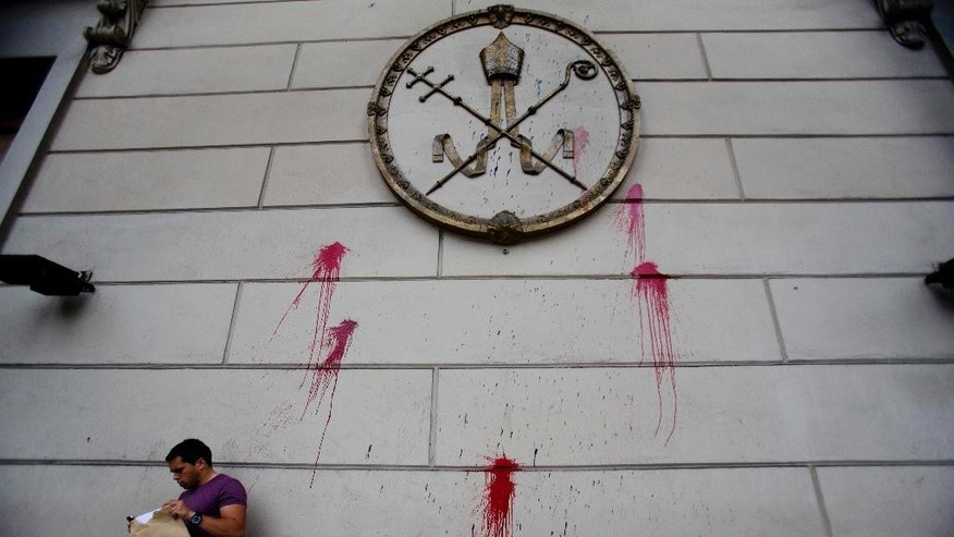 "A man stands outside the Cathedral, which was previously defaced during a protest against gender violence, in Buenos Aires, Argentina, Tuesday, Oct. 25, 2016.  The Vatican and Argentina's bishops have finished cataloguing their archives from the country's ""dirty war"" and will soon make them available to victims and their relatives who have long accused church members of complicity with the military dictatorship. (AP Photo/Natacha Pisarenko)"