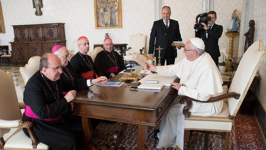 "FILE - In this Oct. 17, 2016 file photo, Pope Francis sits at a table with, from left; Mons. Mario Antonio Cargnello, Archbishop Jose Maria Arancedo, Cardinal Mario Poli, and Mons. Carlos Humberto Malfa, on the occasion of his meeting with the Argentine Episcopal Conference,at the Vatican. The Vatican and Argentina's Catholic Church said Tuesday, Oct. 25, 2016, they had finished cataloguing their archives from the country's brutal ""dirty war"" and will soon make them available to victims and their relatives who have long accused the church of complicity with the military dictatorship.  (L'Osservatore Romano/Pool Photo via AP, files)"