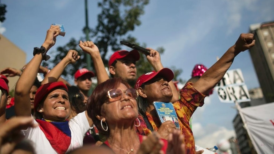 "Supporters of Venezuela's President Nicolas Maduro show their support during a political rally against Congress in Caracas, Venezuela, Tuesday, Oct. 25, 2016. After the government suspended a recall referendum seeking President Nicolas Maduro's removal last week, the opposition-controlled congress began debating his ""constitutional situation."" Lawmakers vow to present evidence that Maduro is a dual Colombian citizen and therefore constitutionally ineligible to hold Venezuela's highest office. (AP Photo/Alejandro Cegarra)"