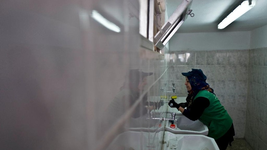 """In this Monday, March 21, 2016 photo, Jordanian plumber Maryam Mutlaq, 41, works in a school in Zarqa. Mutlaq discovered during her training as a plumber that she loved handling tools and fixing things. Even when she was off the clock, she started carrying a few tools in her gray purse, in case a neighbor or relative needed a bit of plumbing """"first aid."""" (AP Photo/Muhammed Muheisen)"""