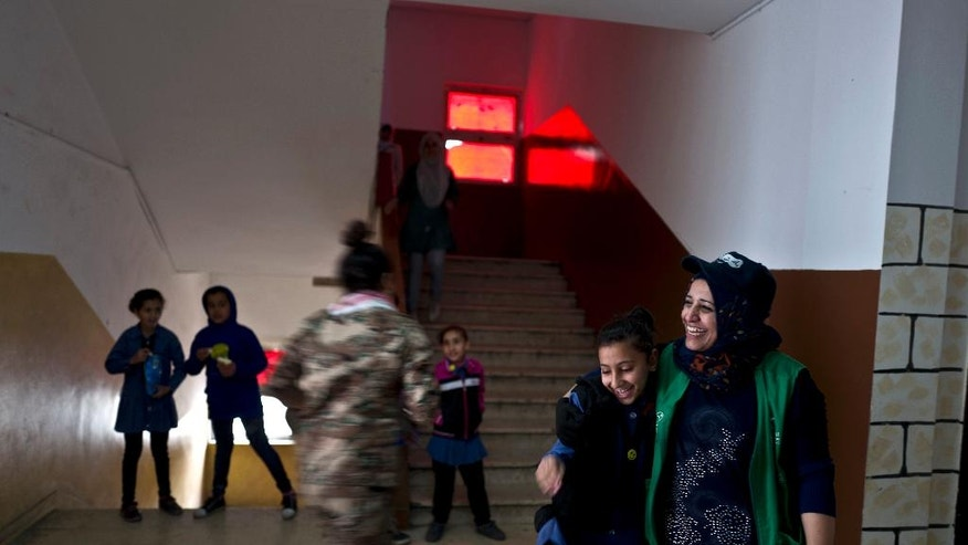"""In this Monday, March 21, 2016 photo, Jordanian plumber Maryam Mutlaq, 41, hugs a student at a school in Zarqa. In the in the afterglow of her graduation from plumber training, she is brimming with optimism. """"We will break down the barriers that have been put up, that say we aren't capable of doing things as women,"""" she says. """"There is also a barrier of fear within us that has to be broken.""""(AP Photo/Muhammed Muheisen)"""