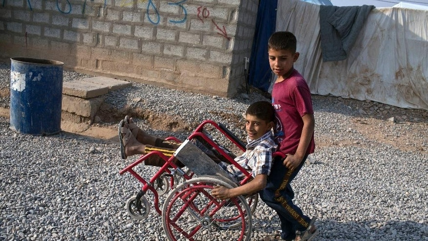 FILE - In this Tuesday, Oct. 25, 2016 file photo, two boys play with a wheelchair at the Baharka camp for displaced persons on the outskirts of Irbil, Iraq. The camp outside Irbil _ the capital of Iraq's largely autonomous Kurdistan region _ houses just a fraction of the more than a million people already uprooted by Islamic State militants in Iraq's north. The camp is home to more than 4,000 people, almost all from Mosul, according to the camp's management. (AP Photo/Marko Drobnjakovic, File)