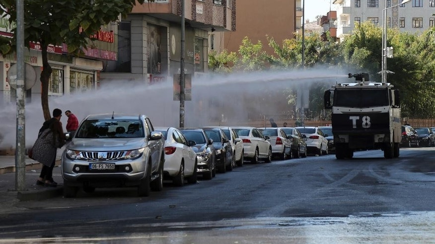 Police use water cannons against pro-Kurdish Peoples's Democratic Party members as they protest the detention of Gultan Kisanak, Diyarbakir Mayor, and co-mayor Firat Anli, in Diyarbakir, Turkey, Wednesday, Oct. 26, 2016. Turkish police on Wednesday used tear gas and water cannons to disperse hundreds of demonstrators protesting the detentions of two leading politicians in the largest city in the country's mainly-Kurdish southeast. About a thousand people gathered outside the Diyarbakir municipality to demand the release of Kisanak and Anli, who were taken into custody late Tuesday as part of a terrorism investigation.(AP Photo/Mahmut Bozarslan)