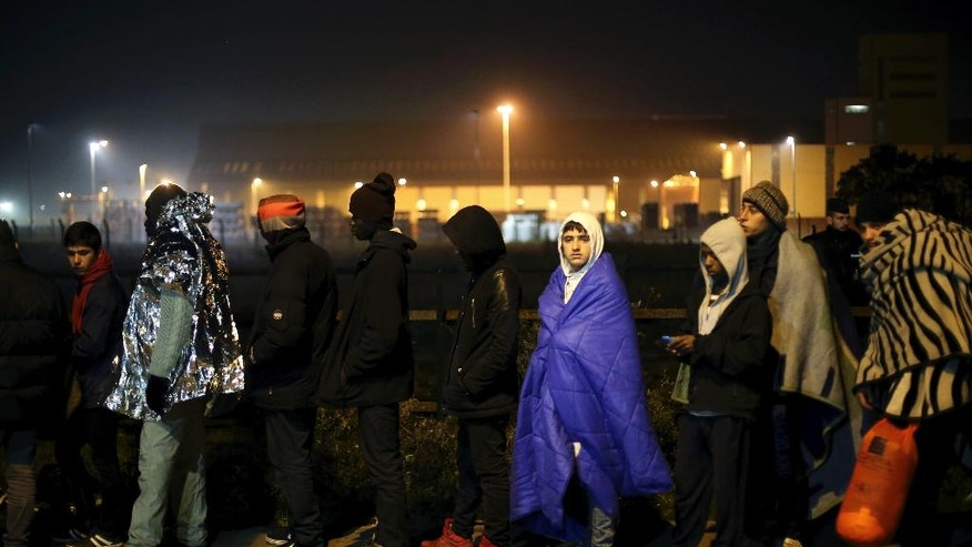 "Migrants wait to register outside a processing centre in the makeshift migrant camp known as ""the jungle"" near Calais, northern France, Wednesday, Oct. 26, 2016. Crews have started dismantling the squalid migrant camp in France after the process to clear the camp began in earnest on Monday. (AP Photo/Thibault Camus)"