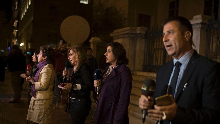 Journalists give a live broadcast to their channels outside the Council of State building in central Athens, Wednesday, Oct. 26, 2016. A high court has canceled a television license auction in Greece, dealing a blow to the country's left-wing government which had carried out the sale.(AP Photo/Petros Giannakouris)