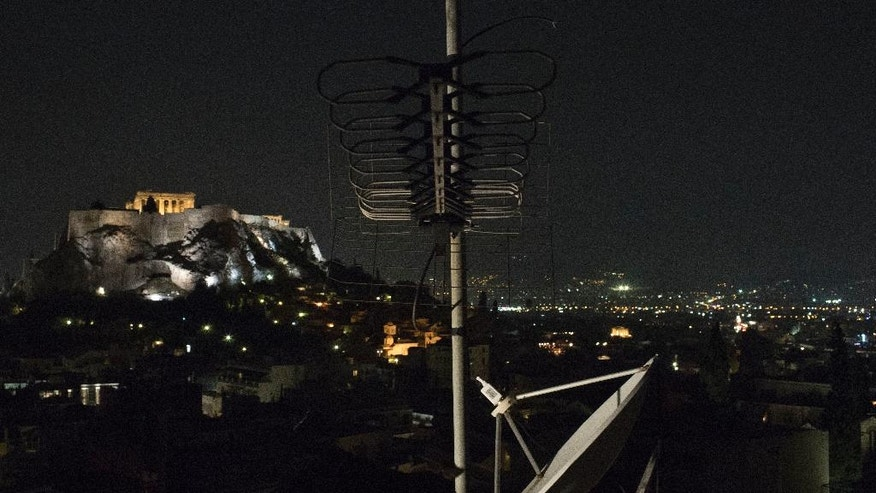 The ancient temple of Parthenon at the Acropolis hill is illuminated in background, behind a satellite dish and TV antenna, in central Athens, Wednesday, Oct. 26, 2016. Council of State judges were expected late Wednesday to rule on the legality of a law passed by Greece's left-led government this year that allowed a tender process for nationwide broadcast licenses, but only two channels have won licenses, and the others are expected to close within weeks. (AP Photo/Petros Giannakouris)