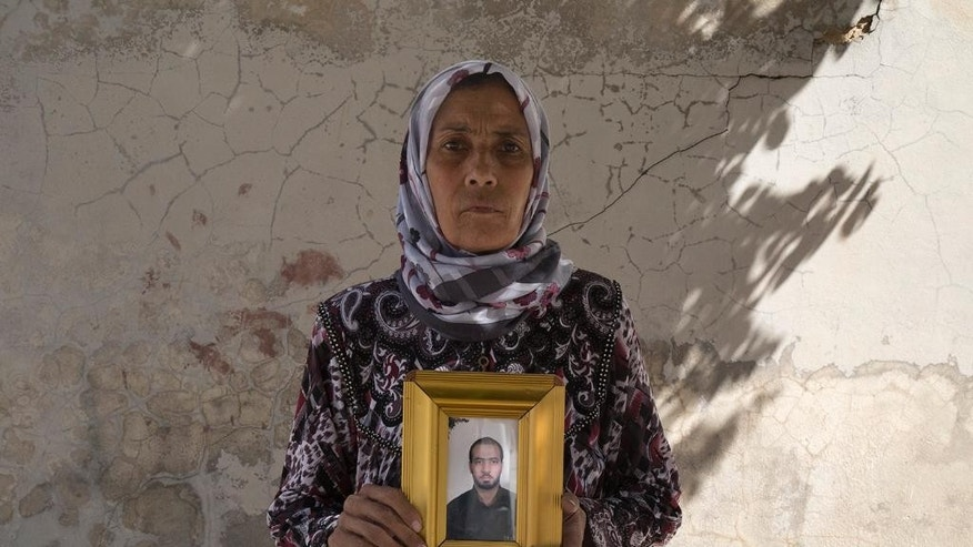 This picture released on Wednesday, Oct. 26, 2016 by the New York-based group Human Rights Watch, shows Zakia Hassan holds a photo of her son, Ibrahim Hammud, 35, who detonated an explosive device when he stepped on a mattress as he returned to his house in Manbij, Syria. Homemade landmines planted by the Islamic State group have killed and injured hundreds of civilians, including dozens of children, in the town of Manbij in northern Syria, Human Rights Watch says. (Ole Solvang, Human Rights Watch via AP)