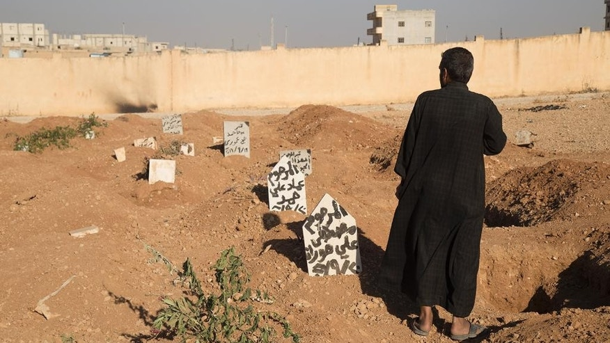 This picture released on Wednesday, Oct. 26, 2016 by the New York-based group Human Rights Watch, shows a family member stands next to the graves of three children who were killed when an explosive device planted by Islamic State group in a school detonated on September 27 in Manbij, Syria. Homemade landmines planted by the Islamic State group have killed and injured hundreds of civilians, including dozens of children, in the town of Manbij in northern Syria, Human Rights Watch says. (Ole Solvang, Human Rights Watch via AP)