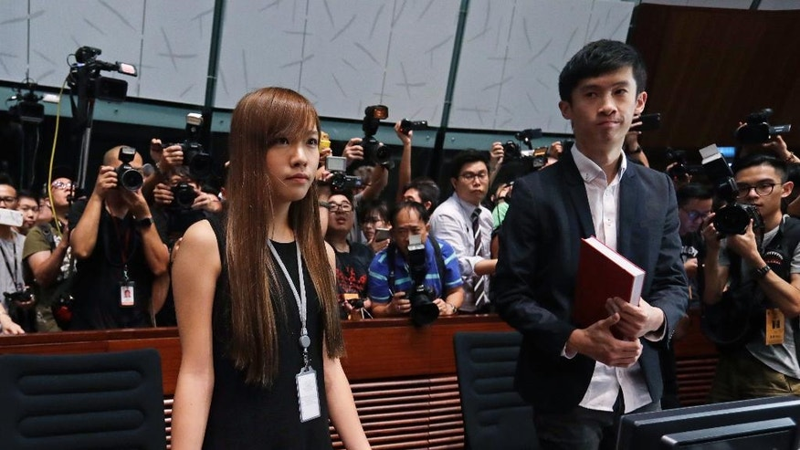 Newly elected Hong Kong lawmakers Yau Wai-ching, left, and Sixtus Leung are surrounded by journalists inside the Legislative chamber in Hong Kong Wednesday, Oct. 26, 2016.   Unruly scenes have gripped Hong Kong's legislature as two newly elected lawmakers defied an order barring them from entering to retake their oaths after being disqualified for swearing and insulting China the first time.  (AP Photo/Kin Cheung)