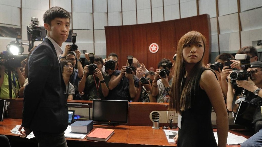 Newly elected Hong Kong lawmakers Yau Wai-ching, right, and Sixtus Leung, left, are surrounded by photographers at legislature council in Hong Kong Wednesday, Oct. 26, 2016.   Unruly scenes have gripped Hong Kong's legislature as two newly elected lawmakers defied an order barring them from entering to retake their oaths after being disqualified for swearing and insulting China the first time. (AP Photo/Vincent Yu)