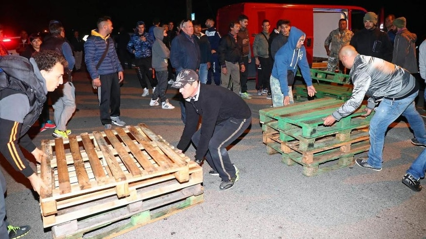 In this picture made available Tuesday, Oct. 25, 2016, protesters try blocking a road with pallets to prevent a bus carrying migrants from passing, in Goro, near Ferrara, Italy. Residents in an Adriatic coastal town posted a blockade overnight to prevent the arrival of 12 female migrants, one of them pregnant, who were to be housed in a hostel, in a sign of growing tension amid persistent migrant arrivals. (Filippo Rubin/ANSA via AP)