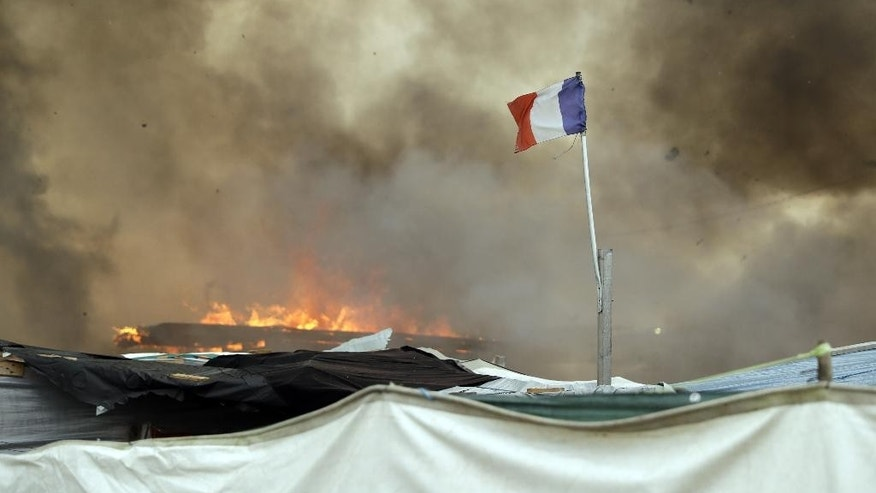 "A French flag flutters while smoke billows from burning shelters set on fire my migrants in the makeshift migrant camp known as ""the jungle"" near Calais, northern France, Wednesday, Oct. 26, 2016. Firefighters have doused several dozen fires set by migrants as they left the makeshift camp where they have been living near the northern French city of Calais. (AP Photo/Matt Dunham)"