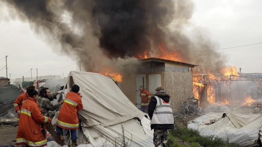 "Charity workers pull tents away from burning shelters set on fire by migrants in the makeshift migrant camp known as ""the jungle"" near Calais, northern France, Wednesday, Oct. 26, 2016. Firefighters have doused several dozen fires set by migrants as they left the makeshift camp where they have been living near the northern French city of Calais. (AP Photo/Matt Dunham)"
