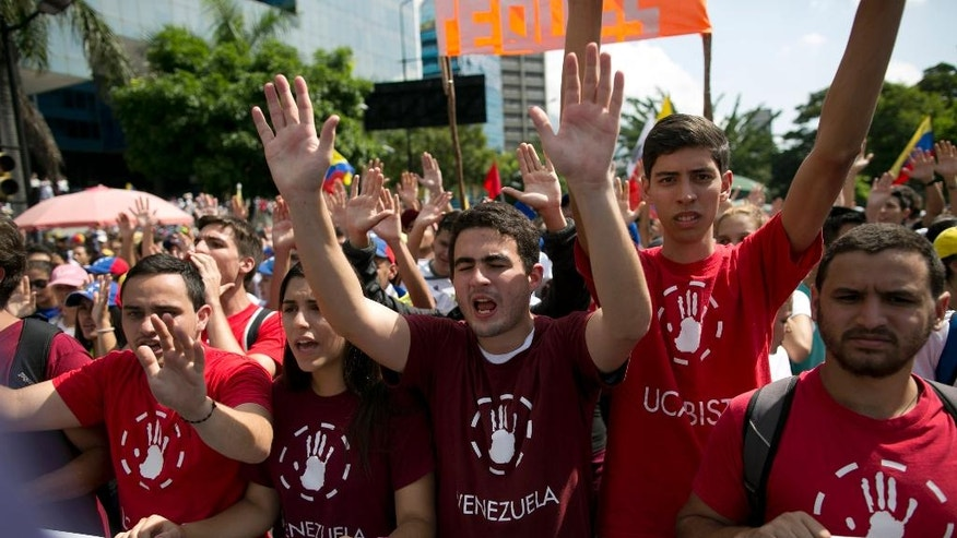 University students protest against President Nicolas Maduro, in Caracas, Venezuela, Wednesday, Oct. 26, 2016. Venezuela's standoff deepened after congress voted to open a political trial against Maduro for breaking the constitutional order and opposition leaders called for mass demonstrations on Wednesday to drive the socialist leader from office.  (AP Photo/Alejandro Cegarra)