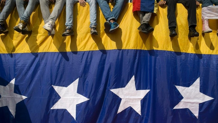 People sit on a wall draped by a Venezuelan national flag during a protest against President Nicolas Maduro, in Caracas, Venezuela, Wednesday, Oct. 26, 2016. Venezuela's standoff deepened after congress voted to open a political trial against Maduro for breaking the constitutional order and opposition leaders called for mass demonstrations on Wednesday to drive the socialist leader from office.  (AP Photo/Alejandro Cegarra)