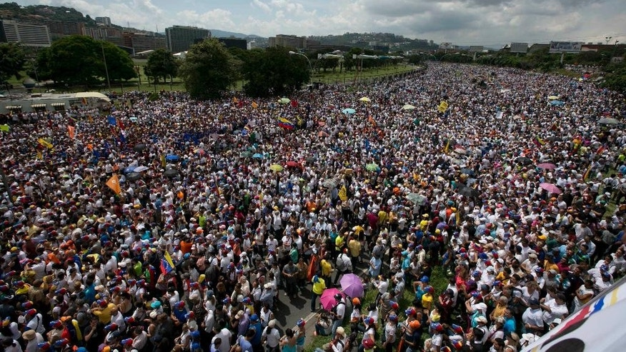 A mass of people take a highway during a protest against President Nicolas Maduro in Caracas, Venezuela, Wednesday, Oct. 26, 2016. Venezuela's standoff deepened after congress voted to open a political trial against Maduro for breaking the constitutional order and opposition leaders called for mass demonstrations on Wednesday to drive the leader from office. Opposition figures say turnout is expected to rival a Sept. 1 rally that drew hundreds of thousands into the street to demand that a recall campaign against President Nicolas Maduro be allowed to proceed. (AP Photo/Ariana Cubillos)
