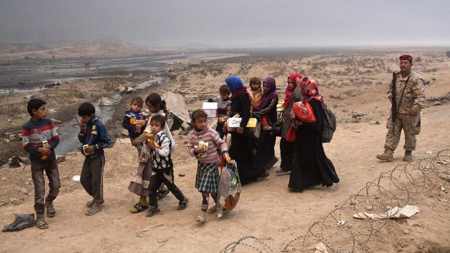 Internally displaced persons clear a checkpoint in Qayara, some 50 kilometers south of Mosul, Iraq, Wednesday, Oct. 26, 2016. Islamic State militants have been going door to door in farming communities south of Mosul, ordering people at gunpoint to follow them north into the city and apparently using them as human shields as they retreat from Iraqi forces. Witnesses to the forced evacuation describe scenes of chaos as hundreds of people were driven north across the Ninevah plains and into the heavily-fortified city, where the extremists are believed to be preparing for a climactic showdown.  (AP Photo/Marko Drobnjakovic)