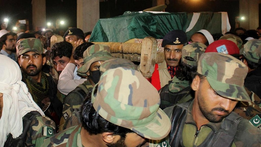 Pakistan army soldiers carry a coffin of their colleague who was killed in an overnight attack on the Quetta Police Training Academy, for burial in Pakistan's tribal area of Shabqadar, Tuesday, Oct. 25, 2016. Militants wearing suicide vests stormed a Pakistani police academy in the southwestern city of Quetta overnight, killing dozens of people, mostly police cadets and recruits, and waging a ferocious gun battle with troops that lasted into early hours Tuesday. (AP Photo/Zia Muhammad)