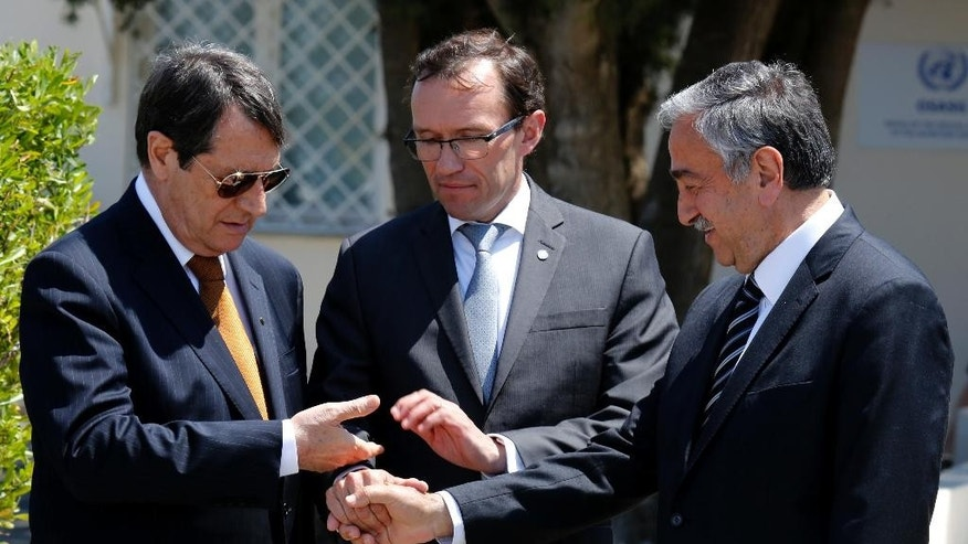 FILE - In this Friday, May 15, 2015 file photo, Cyprus President Nicos Anastasiades, left, Turkish Cypriot leader Mustafa Akinci, right, and United Nations envoy Espen Barth Eide shake hands after their talks at a UN compound inside the the U.N buffer zone at the abandoned Nicosia airport, in the Cypriot divided capital Nicosia, Cyprus. A United Nations spokesman says on Wednesday, Oct. 27, 2016, the leaders of ethnically divided Cyprus' Greek and Turkish speaking communities will conduct a key phase of reunification talks in Mont Pelerin, Switzerland next month Nov. 7-11. Aleem Siddique said the talks between Anastasiades and Akinci will focus on how much territory each side will administer under an envisioned federation. (AP Photo/Petros Karadjias, File)
