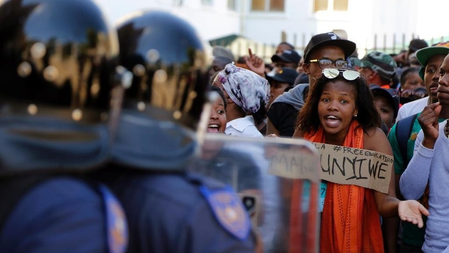 Students protest outside the parliament building in Cape Town, South Africa, Wednesday, Oct. 26, 2016. South African police have used stun grenades to disperse hundreds of protesters who had marched to the parliament building to call for free university education, where the finance minister was giving a budget speech. (AP Photo/Schalk van Zuydam)