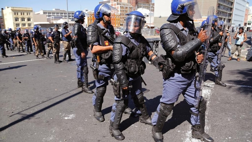 South African Police look towards demonstrators during a protest outside parliament in Cape Town, South Africa, Wednesday, Oct. 26, 2016. South African police have used stun grenades to disperse student protesters outside parliament, where the finance minister was giving a budget speech. (AP Photo/Schalk van Zuydam, Pool)