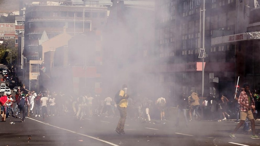 Students run after South African Police fired a stun grenade during a protest outside parliament in Cape Town, South Africa, Wednesday, Oct. 26, 2016. South African police have used stun grenades to disperse student protesters outside parliament, where the finance minister was giving a budget speech. (AP Photo/Schalk van Zuydam, Pool)