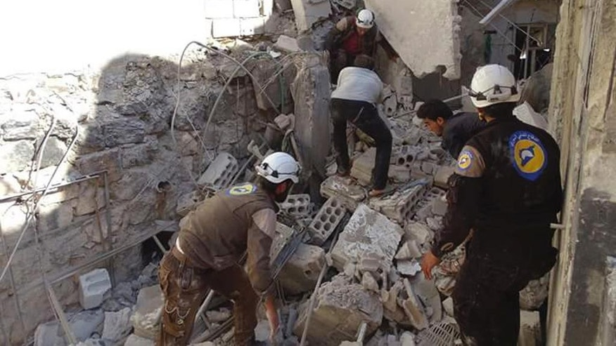 In this photo provided by the Syrian Civil Defense group known as the White Helmets, Syrian Civil Defense workers search through the rubble after airstrikes in the village of Hass in the Idlib province, Syria, Wednesday, Oct. 26, 2016. Syrian activists say that airstrikes outside a school in the northern, rebel-held province of Idlib have killed more than a dozen people, mostly children. The Idlib News network says the airstrikes hit as the children gathered outside a school complex in the village of Hass. (Syrian Civil Defense White Helmets via AP)