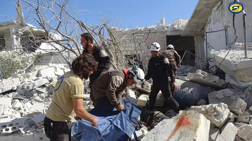 In this photo provided by the Syrian Civil Defense group known as the White Helmets, Syrian Civil Defense workers search through the rubble after airstrikes in the village of Hass in the Idlib province, Syria, Wednesday, Oct. 26, 2016. Syrian activists say that airstrikes outside a school in the northern, rebel-held province of Idlib have killed 17 people, mostly children. The Idlib News network says the airstrikes hit as the children gathered outside a school complex in the village of Hass. (Syrian Civil Defense White Helmets via AP)