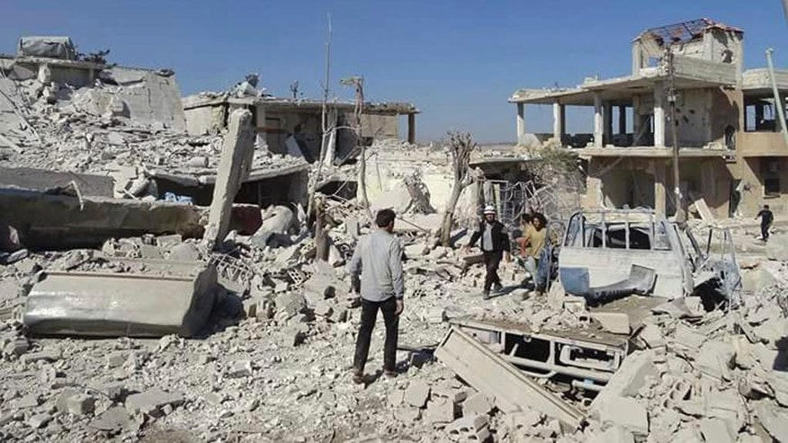 In this photo provided by the Syrian Civil Defense group known as the White Helmets, Syrians inspecting damaged buildings after airstrikes in the village of Hass in the Idlib province, Syria, Wednesday, Oct. 26, 2016. Syrian activists say that airstrikes outside a school in the northern, rebel-held province of Idlib have killed more than a dozen people, mostly children. The Idlib News network says the airstrikes hit as the children gathered outside a school complex in the village of Hass. (Syrian Civil Defense White Helmets via AP)