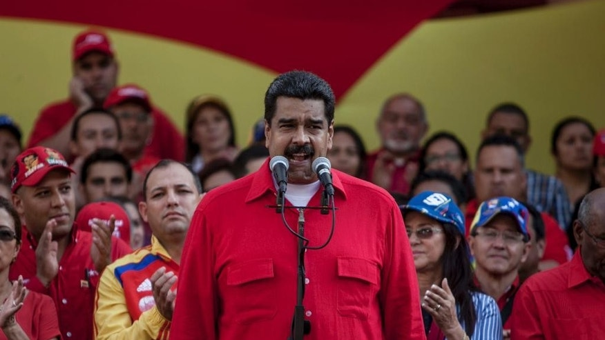 "Venezuela's President Nicolas Maduro speaks during a political rally against the Congress in Caracas, Venezuela, Tuesday, Oct. 25, 2016. After the government suspended a recall referendum seeking Maduro's removal last week, the opposition-controlled congress began debating his ""constitutional situation."" Lawmakers vow to present evidence that Maduro a dual Colombian citizen and therefore constitutionally ineligible to hold Venezuela's highest office. (AP Photo/Alejandro Cegarra)"