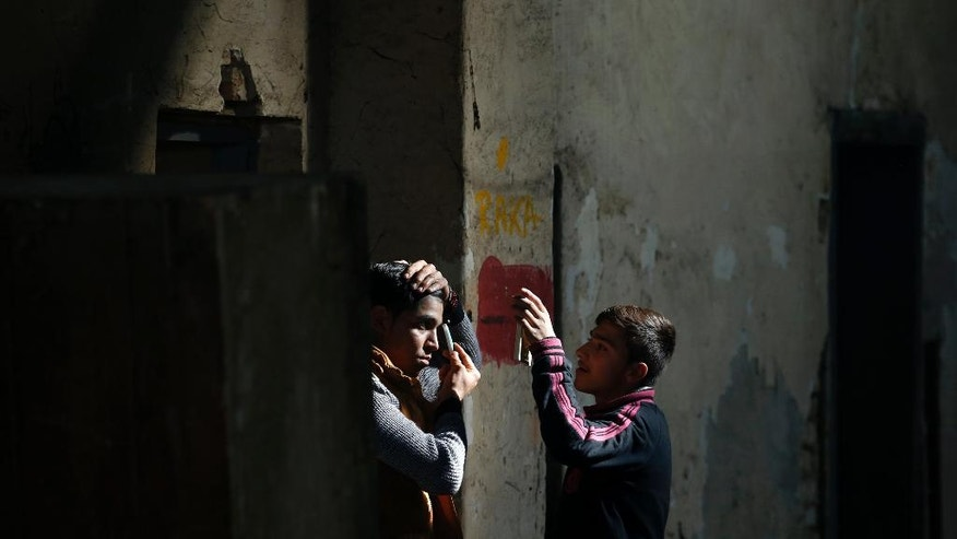 A migrant shaves while another holds up a mirror for him inside an abandoned warehouse in Belgrade, Serbia, Thursday, Oct. 27, 2016. More than 200 migrants have turned a former warehouse in central Belgrade into their temporary home. Several thousand migrants are stuck in Serbia looking for ways to cross into the European Union using clandestine routes and the help of people smugglers. (AP Photo/Darko Vojinovic)