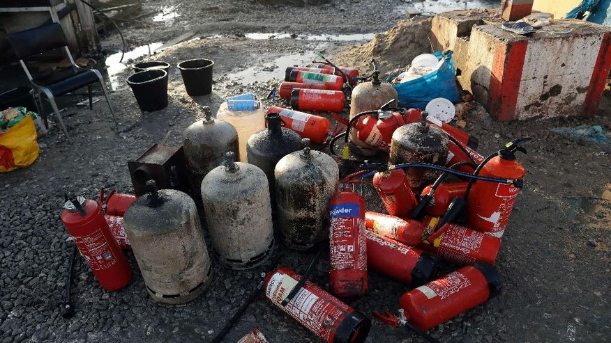 "Gas canisters and fire extinguishers are stacked up inside the makeshift migrant camp known as ""the jungle"" near Calais, northern France, Thursday, Oct. 27, 2016. French authorities claimed on Wednesday that they had cleared the makeshift migrant camp near the northern French city of Calais. (AP Photo/Matt Dunham)"