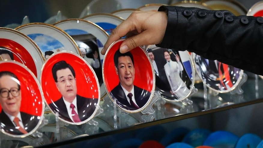 A worker takes a porcelain plate bearing an image of Chinese President Xi Jinping for a customer which on display together with previous leaders Jiang Zemin, left, and Hu Jintao, second left, at a souvenir shop near Tiananmen Square in Beijing, Thursday, Oct. 27, 2016. China's ruling Communist Party concludes a key meeting this week aimed at shoring up internal discipline and asserting General Secretary Xi Jinping's authority. The gathering is also expected to lay the groundwork for next year's national congress that will decide major leadership positions and lay out the agenda for Xi's next five-year term. (AP Photo/Andy Wong)