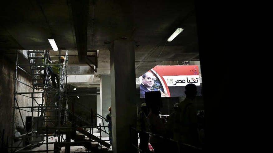 "A worker stands near a large poster of Egyptian President Abdel-Fattah el-Sissi with Arabic that reads, ""long live Egypt,"" as the National Authority for Tunnels holds a press conference on the progress of the third line of the Cairo metro, in Egypt, Thursday, Oct. 27, 2016. Egypt hopes to attract much needed investment when it unleashes market forces with devaluation, subsidy cuts and reforms aimed at bringing an IMF bailout. But fears of a backlash from a public already straining under high inflation and unemployment are growing. (AP Photo/Nariman El-Mofty)"