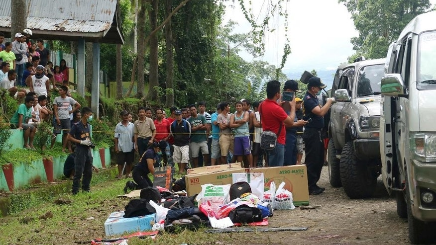 Residents watch as police inspect the contents of the vehicles following an operation Friday, Oct. 28, 2016 at Makilala township, North Cotabato province in southern Philippines. Philippine police say Mayor Samsudin Dimaukom of southern Datu Saudi Ampatuan township and nine others were killed before dawn in a gunbattle with anti-narcotics officers in one of the deadliest operations since President Rodrigo Duterte launched a crackdown on illegal drugs. According to Superintendent Bernard Tayong, Dimaukom has been named by Duterte as among many politicians suspected to be involved in illegal drugs.(AP Photo)