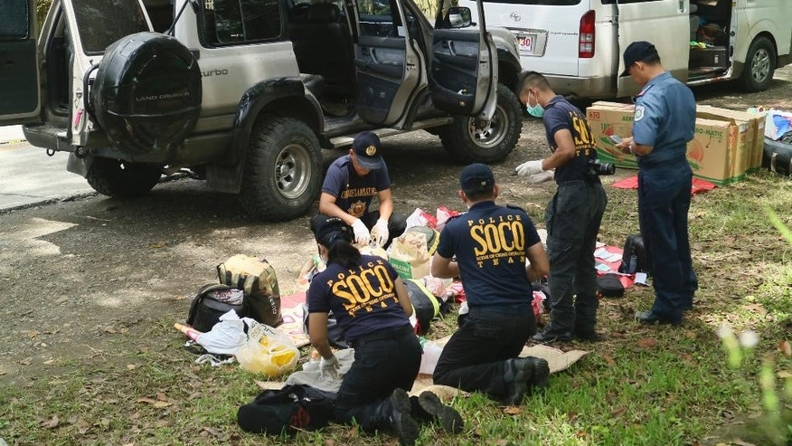 Police inspect the contents of the vehicles following an operation Friday, Oct. 28, 2016 at Makilala township, North Cotabato province in southern Philippines. Philippine police say Mayor Samsudin Dimaukom of southern Datu Saudi Ampatuan township and nine others were killed before dawn in a gunbattle with anti-narcotics officers in one of the deadliest operations since President Rodrigo Duterte launched a crackdown on illegal drugs. According to Superintendent Bernard Tayong, Dimaukom has been named by Duterte as among many politicians suspected to be involved in illegal drugs.(AP Photo)