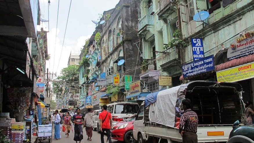 "In this Oct. 3, 2016 photo, people walk in a downtown shopping street lined with old colonial buildings used as shops, restaurants and houses in Yangon, Myanmar. The Yangon Heritage Trust says Myanmar's largest city and commercial capital is facing its ""last best chance"" to salvage and restore many crumbling colonial treasures. They recently proposed a ""heritage strategy"" for the city that outlines a vision of how to make the city more livable, modern and still affordable as property developers crowd in, while preserving its unique landmarks and neglected green spaces. (AP Photo/Elaine Kurtenbach)"